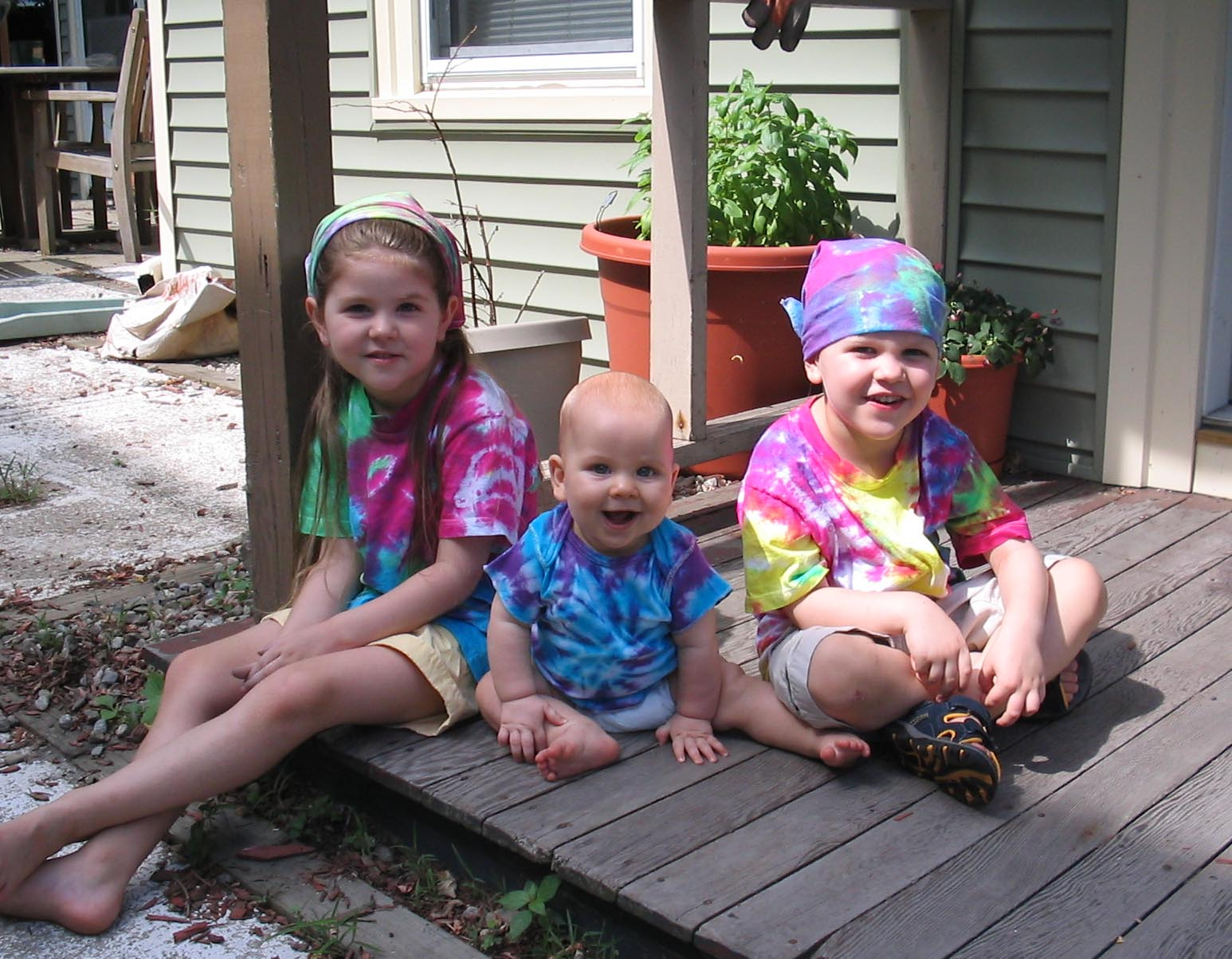 Three white children sitting on a porch wearing various tye-dye clothing.