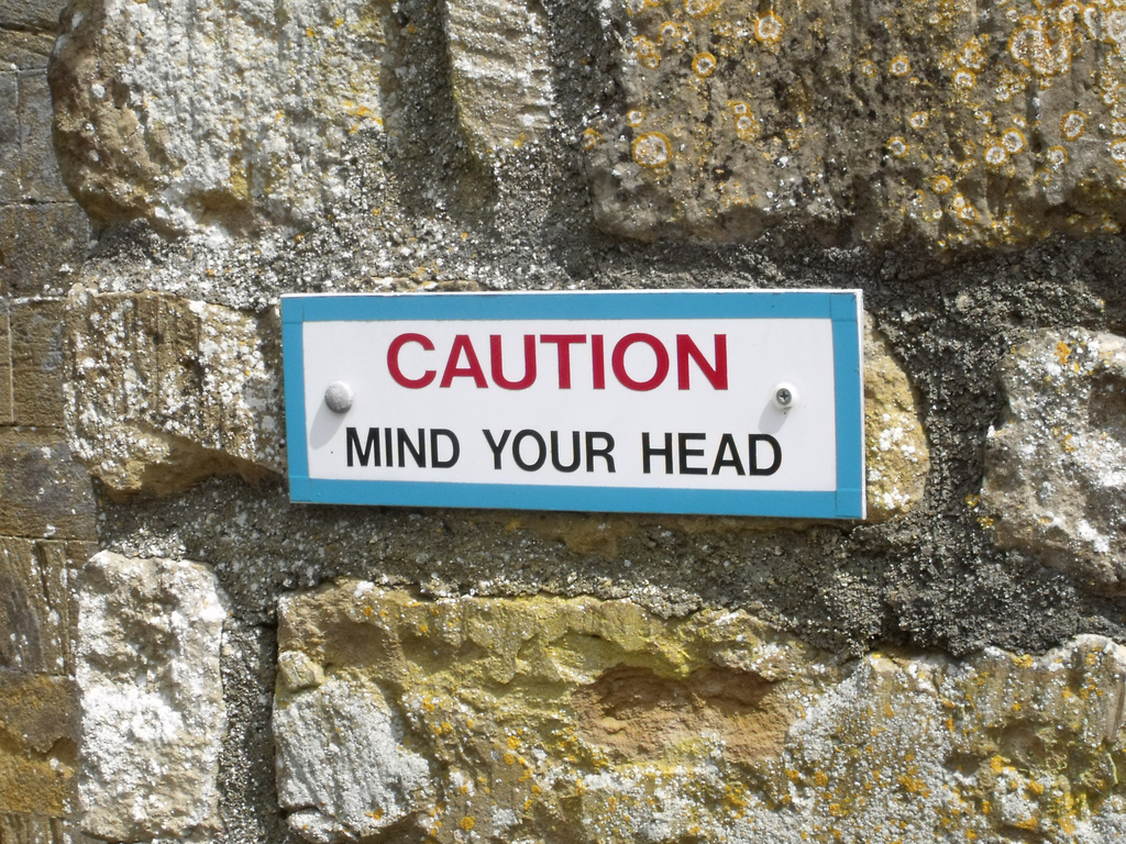 "A sign, reading ""Caution, Mind Your Head"" is mounted on a wall made of large flat stones."